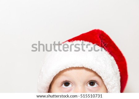 Child close-up in Santa Claus red and white hat looking up in curiosity isolated on white background with free space