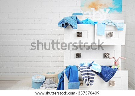 Child clothes in wooden chest of drawer, close up - stock photo