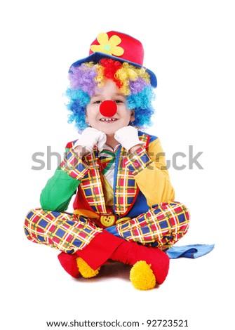Child clown sitting on the floor - stock photo