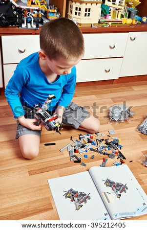Child collects plastic building kit on wooden floor