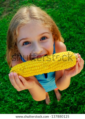 Child, corn - lovely girl eating corn on the cob  in the garden - stock photo