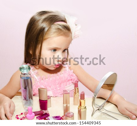 Child cosmetics  Cute little girl looking in the mirror isolated - stock photo