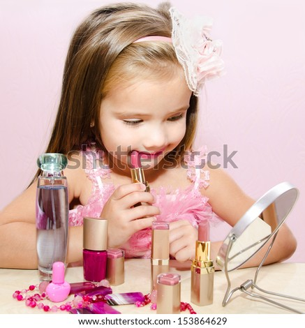 Child cosmetics  Cute little girl with lipstick and  mirror isolated - stock photo