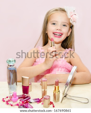 Child cosmetics  Cute little girl with lipstick isolated - stock photo