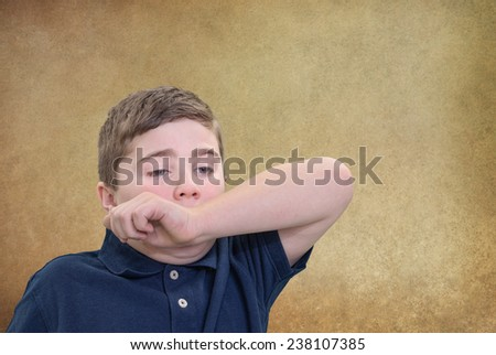 Child Covering his Mouth with his Arm to Stifle Sneeze or Yawn - stock photo