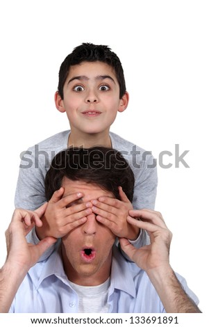 Child covering parent's eyes - stock photo