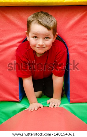 Child crawling through tunnel on play mats - stock photo