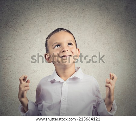 Child crossing fingers. Young man making wish, hopeful, looking up isolated grey wall background. Human face expressions, emotions, feelings, body language, signs, symbols - stock photo