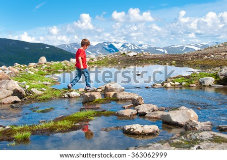Child crossing mountain lake in Norway