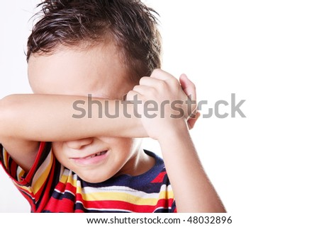 Child crying covering his face with his hand.