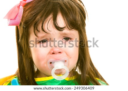 Child crying with pacifier in the mouth - stock photo
