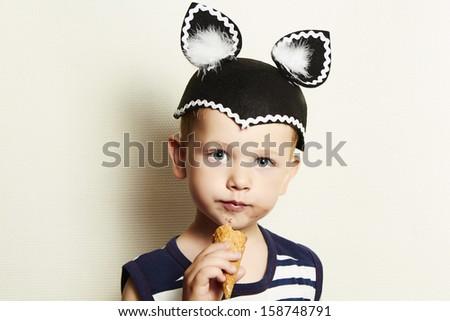 Child. cute kid boy eating ice cream in studio.masquerade - stock photo