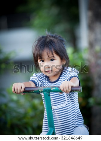 Child cute little girl riding on seesaw in playground - stock photo