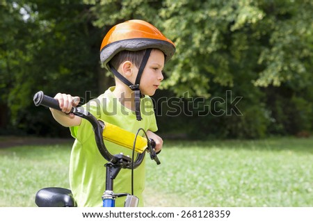 Child cyclist, portrait of a boy pushing his bicycle in a green park. - stock photo