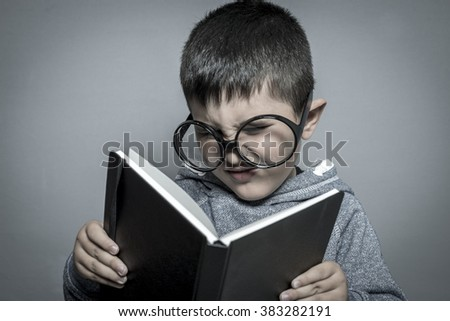 child, dark-haired young student reading a funny book, reading and learning