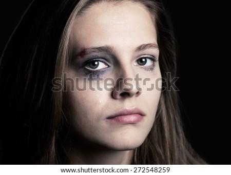 Child. Dark portrait of a crying teen girl, studio shot - stock photo