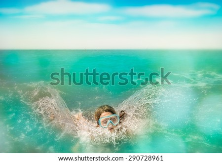 child dip and swim in the water, cloudy and blue sky - stock photo