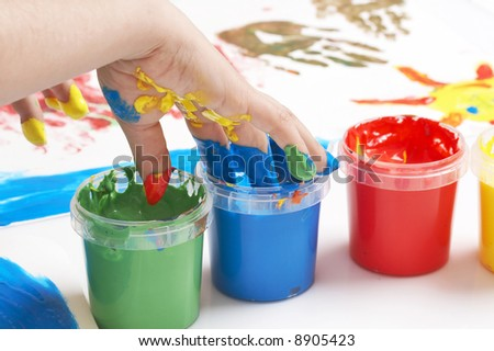 child dipping fingers in painting colors - stock photo