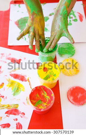 Child dipping fingers in washable, non-toxic finger paints, painting a drawing. Sensory play, innovative approach to learning, fun childhood, back to school concept. - stock photo