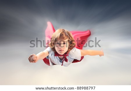 Child disguised as a superhero flying in the sky - stock photo