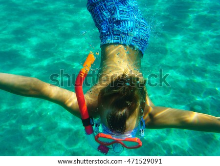 Child diver with mask swimming underwater in sea.