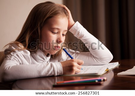 Child doing homework. Sad girl writing, reeding - stock photo