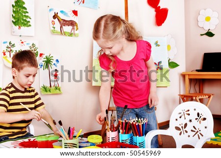 Child  draw paints in play room. Preschool. - stock photo