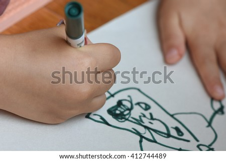 child drawing a figure with small hand