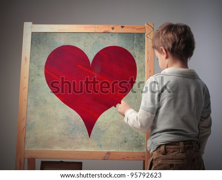 Child drawing a heart on a blackboard - stock photo