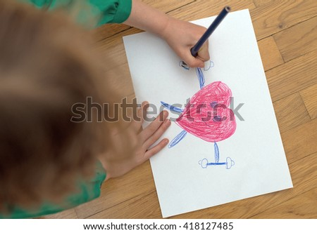 Child drawing funny sporty red heart on paper. - stock photo