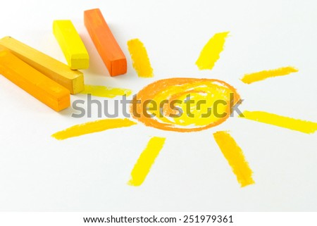 Child drawing of sun using oil pastel crayon - stock photo