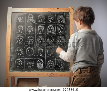 Child drawing some portraits of a blackboard - stock photo