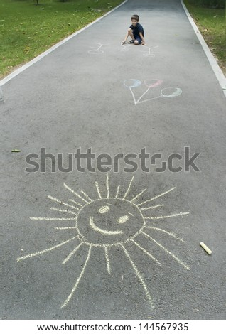 Child drawing sun on asphalt in a park - stock photo
