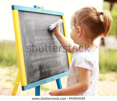 Child drawing with chalk at the blackboard - stock photo