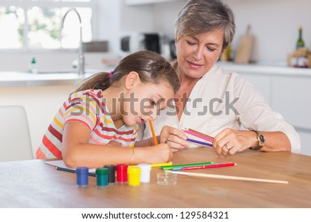 Child drawing with her grandmother in kitchen - stock photo