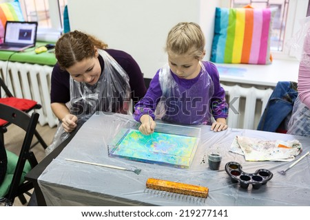 Child drawing with needle on the water. Ebru art is a method of aqueous surface design - stock photo