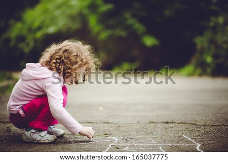 Child draws on asphalt - stock photo
