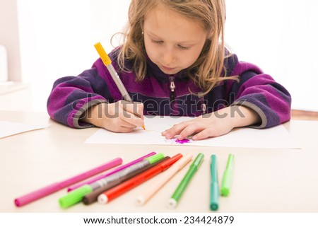 Child draws the picture. Blurred pens on the foreground