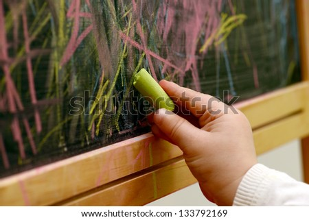child draws with chalk on a blackboard - stock photo