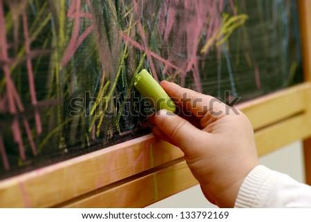 child draws with chalk on a blackboard - stock photo
