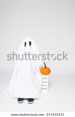 child dressed in a cute ghost costume sitting with a pumpkin