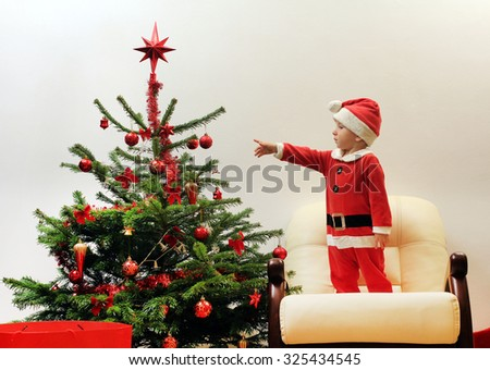 Child dressed in Santa Claus near the Christmas tree - stock photo