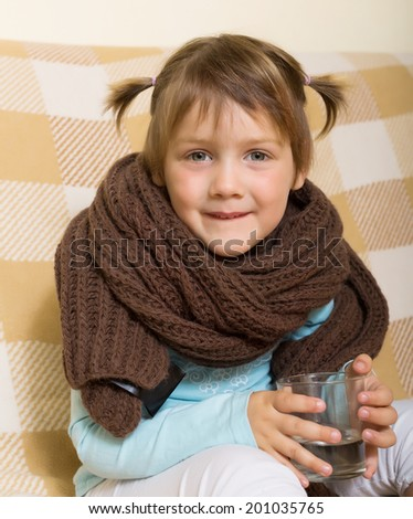 Child dressed in scarf drinking from glass   - stock photo