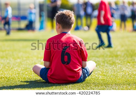 Child dressed in sports clothes sitting on green grass of sports stadium. Boys is waiting on his turn to play soccer football match. - stock photo