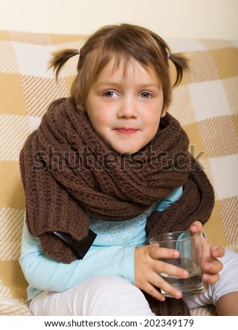 Child dressed in warm  scarf drinking from glass   - stock photo