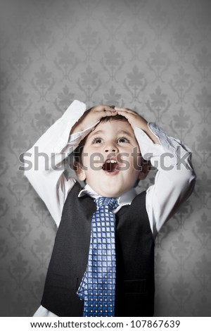 child dressed like businessman with hands on head and face of surprise