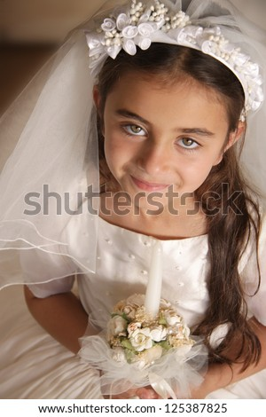Child dressed up for her first communion with white dress and veil - stock photo