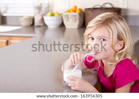 child drinking glass of milk with straw sitting in kitchen at home