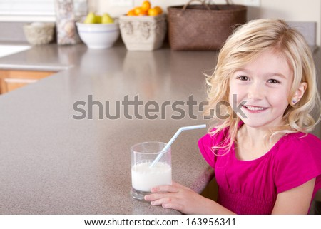 child drinking glass of milk with straw sitting in kitchen at home - stock photo