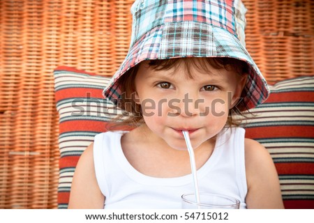 child drinking juice through a straw - stock photo